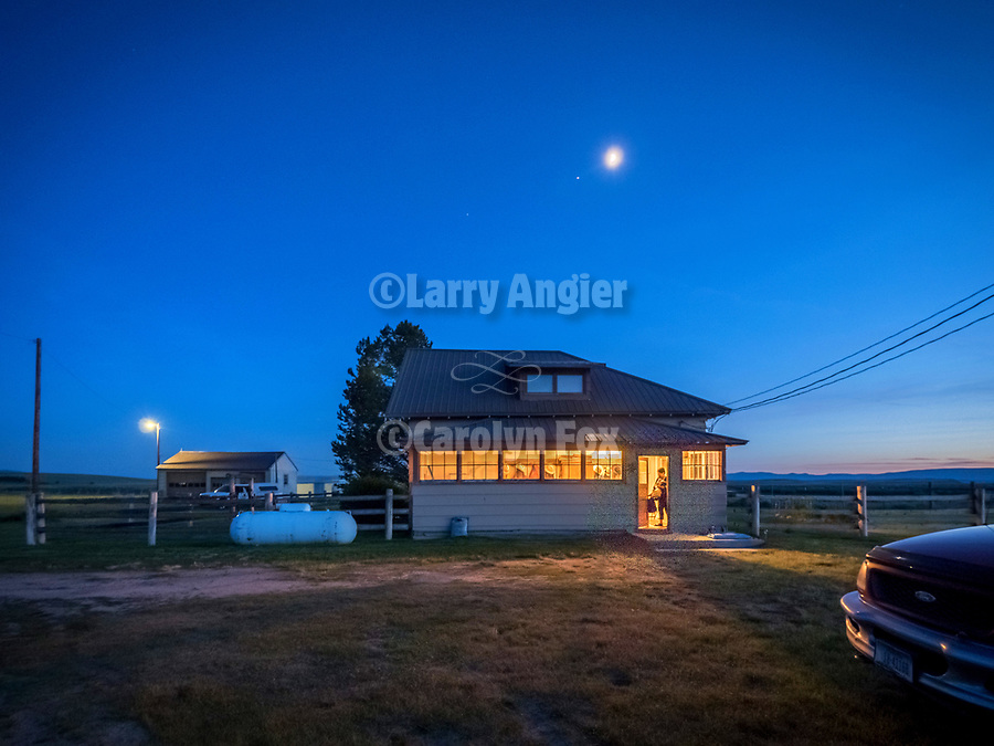 First quarter moon over the Daniels Ranch house in an early summer evening, Wisdom, Montana