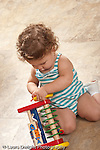 13 month old baby girl at home kneeling on floor exploring colorful wooden new toy vertical