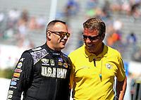 Jun 7, 2015; Englishtown, NJ, USA; NHRA top fuel driver Tony Schumacher (left) talk with a Safety Safari member during the Summernationals at Old Bridge Township Raceway Park. Mandatory Credit: Mark J. Rebilas-