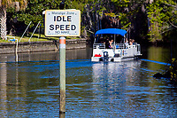 Curious visitors in a variety of watercraft observe the Idle Speed No Wake signs in respect for the protection of the endangered Florida Manatees that frequent the warm waters near Crystal River,Florida.