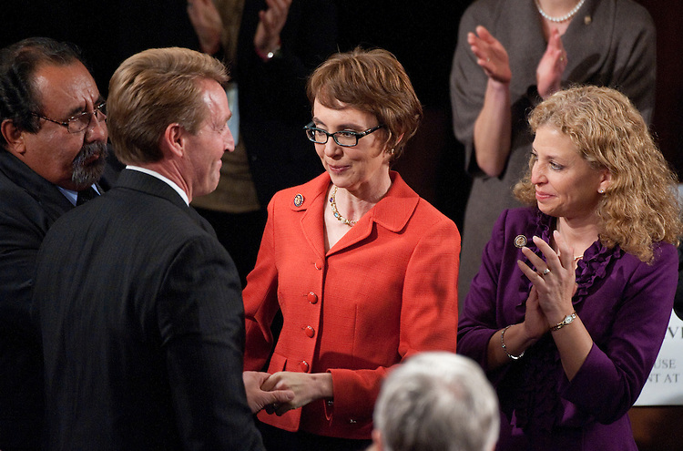UNITED STATES - JANUARY 24:  Rep. Gabrielle Giffords, D-Ariz., center, is greeted by Rep. Jeff Flake, R-Ariz., upon arriving to the House floor before the start of President Barack Obama's State of the Union Address before a joint session of Congress in the U.S. Capitol.  Reps. Raul Grijalva, D-Ariz., far left, and Debbie Wasserman Schultz, D-Fla., also appear. (Photo By Tom Williams / CQ Roll Call)