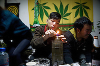 Jobby, of the punk band Overdose, (right) and Zhou Ge, of the psychobilly band The Angry Jerks, smoke marijuana from a bong made of a soda bottle in a tattoo parlor in Nanjing, China.