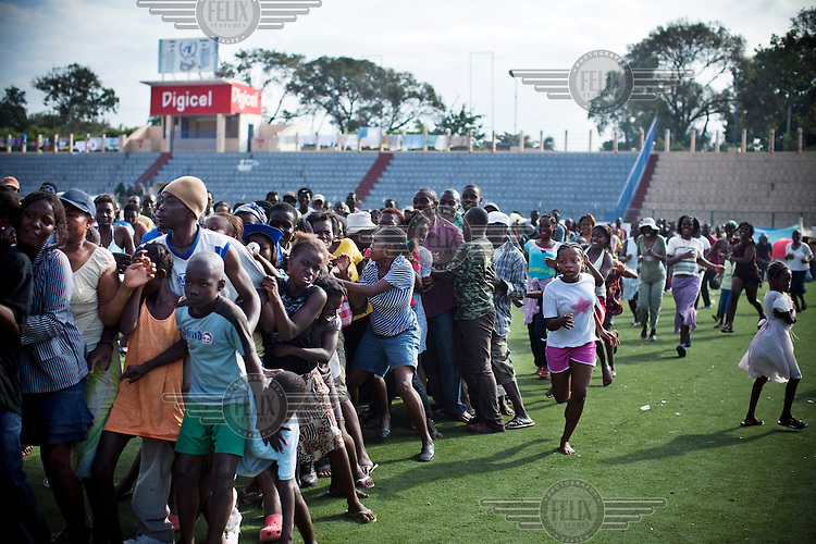 People jostle for position as they queue for food distibution organised by the World Food Programme (WFP) in the city's main stadium. A 7.0 magnitude earthquake struck Haiti on 12/01/2010. Early reports indicated that more than 100,000 may have been killed and three million affected.