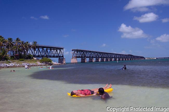 bathe floats on an airmatress in the waters off Caloosa Beach, Bahia Honda St Pk, Florida Keys.  Old Flagler RR trestle bridge is in background