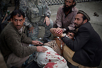 Khan Bacha, from Assadabad, an Afghan worker on the US Army Korengal Outpost is helped after being wounded by a mortar and grenade attack on the base in the restive Korengal Valley. Khan was treated for shrapnel wounds to his leg, back, shoulder and face on the base by US Army medics and was then medevaced to a US Army hospital in Jalalabad for further treatment.