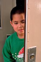 Boy age 7 peeking out of doorway entrance.  Western Springs  Illinois USA