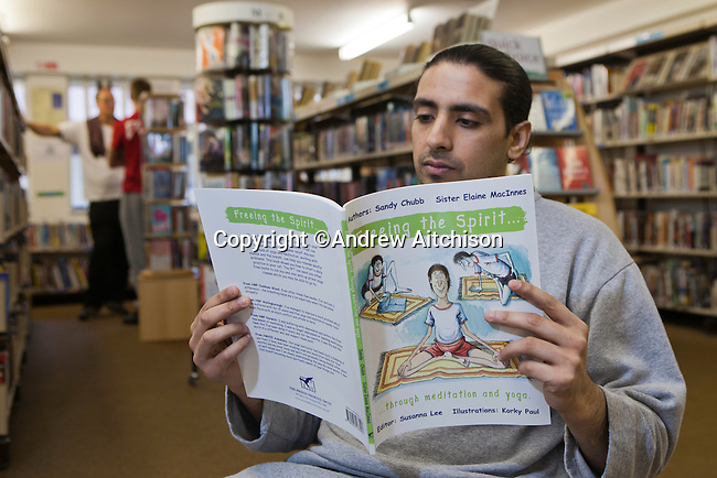 A prisoner reads a book in the prison library about yoga printed by the Prison Phoenix Trust. HMP Bullingdon, Oxfordshire.