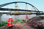ROTTERDAM - In het Europoortgebied fotografeert een medewerker van bruggenbouwer Hollandia uit Krimpen a/d IJssel zijn collega tijdens het transport per drijvende pontons van de Dintelhavenbrug, de eerste spoorbrug van de Betuweroute. Op vijfhonderd meter van zijn nieuwe ligplaats is de 270 meter lange brug het afgelopen jaar in segmenten opgebouwd waarna het vierduizend ton zware gevaarte maandagochtend bij laag water voorzichtig het water opgereden is om op zijn plaats getild te worden. Naast de spoorbrug die door het ontbreken van een middenpijler zesbaks-duwvaart mogelijk maakt, komt nog een door CFE te bouwen verkeersbrug te liggen. COPYRIGHT TON BORSBOOM