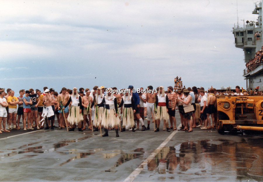BNPS.co.uk (01202 558833)Pic: Bosleys/BNPS<br /> <br /> King Neptune's court.<br /> <br /> Never-before-seen photos have emerged to show the hilarious moment Prince Andrew was mercilessly ridiculed as part of a Royal Naval initiation 36 years ago.<br /> <br /> The young officer was made to take part in a Crossing the Line ceremony to mark the first time he passed the equator as a seaman.<br /> <br /> In a nod to Prince Andrew's Royal background, the photos show him sat on makeshift throne with a cardboard crown placed on his head.<br /> <br /> Alarmingly, a seaman dressed as the barber is seen approaching the then second-in-line to the throne with a very large meat clever covered in imitation blood.