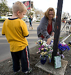 A women and her son put flowers near the scene of a shooting that killed four Lakewood Police Officers in Lakewood on Sunday, Nov. 29, 2009.  At about 8:00 this morning, a gunman walked into the Fornza Coffee shop while the four police officers were having coffee before their shift started and opened fire, killing all our law enforcement.Jim Bryant Photo. ©2010. ALL RIGHTS RESERVED.