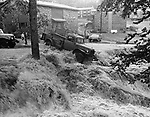 Swirling waters attempt to carry away a truck along its path of destruction in front of Bunker Hill Apartments in Waterbury, June 1973.