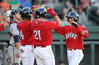 Javier Guerra (31) of the Greenville Drive, right, is congratulated by Yoan Moncada (24) and Nick Longhi (21) after scoring a run in a game against the Rome Braves on Friday, June 12, 2015, at Fluor Field at the West End in Greenville, South Carolina. Guerra is the No. 13 prospect of the Boston Red Sox, according to Baseball America. (Tom Priddy/Four Seam Images)
