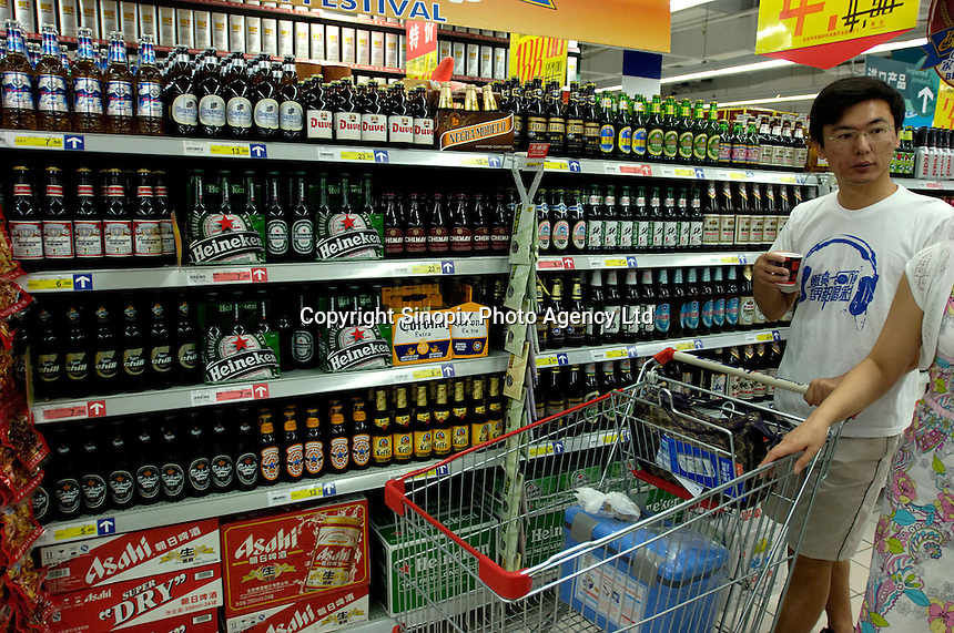 A man tastes beer at Heineken, Corona, Budweiser and other brand beers shelves in a Carrefour supermarket in Beijing, China. Major international chains like Carrefour and Walmart Stores have expanded aggressively in China. Local Chinese retailers have loudly protested this and lobbied heavily for protection from the new competition in price and service that these major retailers have set off..23 Jul 2006