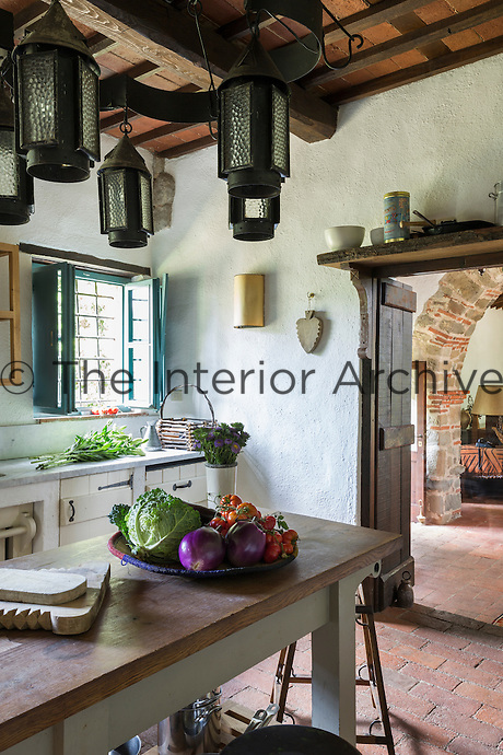 Arts and Crafts lanterns and Carrara marble worktops in the kitchen. Traditional local materials were kept during the restoration of the house, such as the terracotta tiles on the floor and ceilings and the original massive wooden beams.