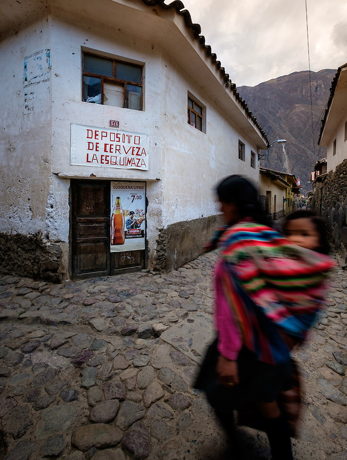 OLLANTAYTAMBO, PERU - CIRCA OCTOBER 2015:  Woman carrying child in the streets of Ollantaytambo, a small village in the Cusco region known as Sacred Valley