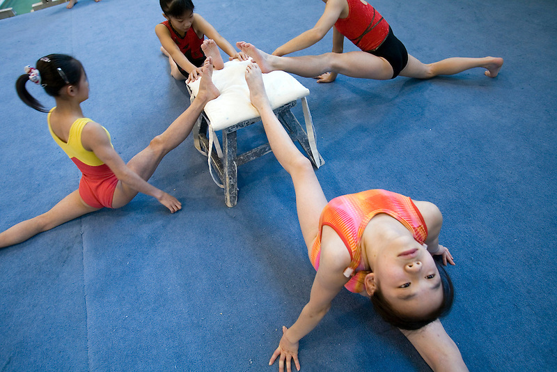Chinese girls stretch before a workout during an afternoon training session of the Beijing Gymnastic team.