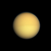Seasonal changes in the atmosphere of Saturn's largest moon are captured in this natural color image, which shows Titan with a slightly darker top half and a slightly lighter bottom half. Titan's atmosphere has a seasonal hemispheric dichotomy, and this image was taken shortly after Saturn's August 2009 equinox. Images taken using red, green and blue spectral filters were combined to create this natural color view. Scientists have found that the winter hemisphere typically appears to have more high-altitude haze, making it darker at shorter wavelengths (ultraviolet through blue) and brighter at infrared wavelengths. The switch between dark and bright occurred over the course of a year or two around the last equinox. Scientists are studying the mechanism responsible for this change, and will monitor the dark-light difference as it flip-flops now that the 2009 equinox has signaled the coming of spring and then summer in the northern hemisphere..Although this hemispheric boundary appears to run directly east-west near the equator, its position is not level with latitude and is actually offset from the equator by about 10 degrees of latitude. This view looks toward the Saturn-facing side of Titan (5,150 kilometers, or 3200 miles across). North on Titan is up.  The images were obtained with the Cassini spacecraft wide-angle camera on Aug. 25, 2009 at a distance of approximately 174,000 kilometers (108,000 miles) from Titan. Image scale is 10 kilometers (6 miles) per pixel..Credit: NASA-JPL-Space Science Institute via CNP