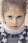 A blonde girl with blue eyes poses for a camera. Photo by Sanad Ltefa