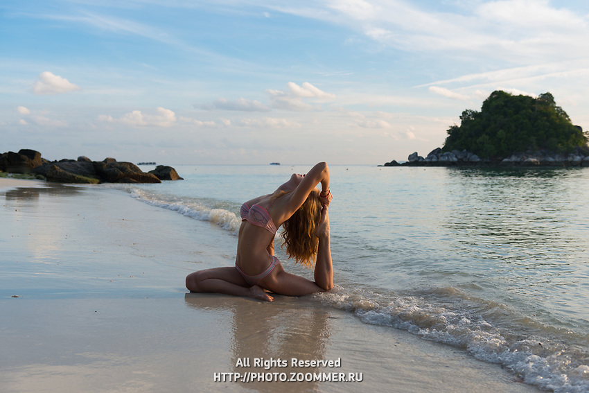 Beach yoga girl in pigeon pose on Thailand empty beach, Ko Lipe