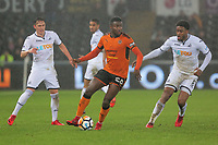 Bright Enobakhare of Wolverhampton Wanderers (C) against Connor Roberts of (L) and Leroy Fer (R) during the Emirates FA Cup match between Swansea and Wolverhampton Wanderers at the Liberty Stadium, Swansea, Wales, UK. Wednesday 17 January 2018