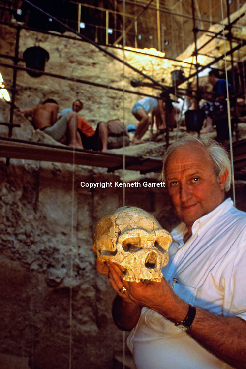 French prehistorian Henry de Lumley, Holds a partial skull reconstruction and 400,000 year old fossil, Arago cave, Pyrenees, France,.