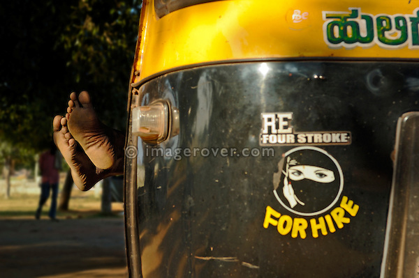 A tuktuk (autorikshaw, scooter) driver having a sleep - his feet sticking outside. Hampi, Karnataka, India.
