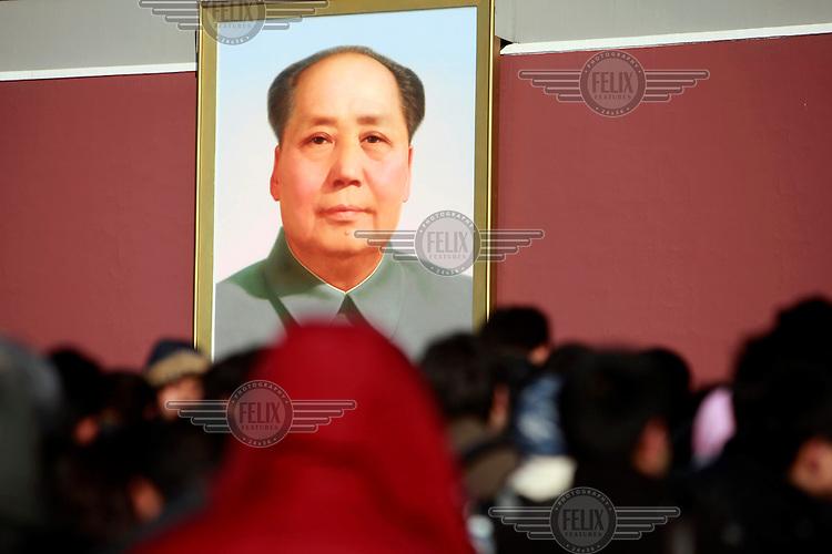 people walk beneath a portrait of Mao Zedong (Mao Tse-tung) in Tiananmen Square.