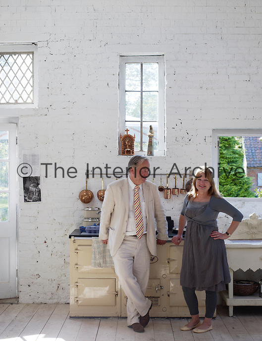 Sheila Scholes and her husband photographed next to the old-fashioned Aga in the large yet cosy kitchen  of their Arts and Crafts house in Norfolk