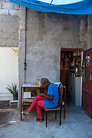 Haiti, Port-au-Prince, Artisan business, Atellier Calla , founded by Christelle Chignard Paul. Original handmade jewelry made from cow horn. Young woman working in the shop. MR