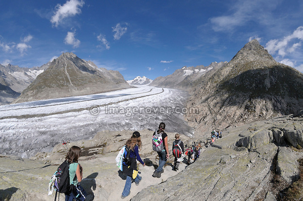 Switzerland, Valais, Western Europe, Jungfrau Region, Aletsch Glacier (UNESCO world heritage site). Teenage hikers on the panorama trail descending to the Märjelensee. Note: No releases available.
