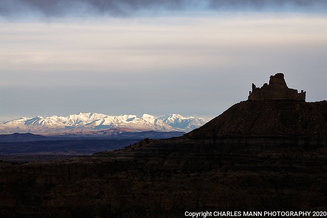 Angel Peak is silhoutted against the snow covered La Plata Mountains on an October morning at Angel Peak National Recreation Area.