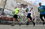 Participants run along Israel's controversial separation barrier, which divides the West Bank from Jerusalem, in the biblical West Bank town of Bethlehem during the 5th Palestine Marathon on March 31, 2017. Photo by Wisam Hashlamoun