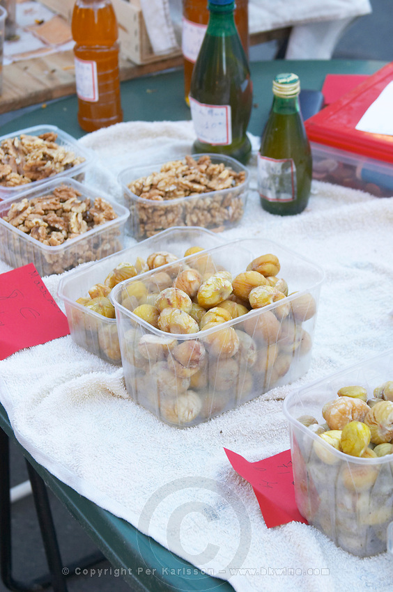 Peeled chestnuts and opened cracked walnuts sold in plastic trays on a street market stand Bergerac Dordogne France