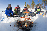 Sweden, SWE, Kiruna, 2008Mar26: Barbecue in Lapland: Three women and a man in their fourties together with two children grill some sausages above an open fire in the snow.