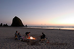 Cannon Beach is located west of Highway 101 in the approximately three blocks between the highway and the Pacific Ocean in Clatsop County on the Northern Oregon Coast.  Visible in the distance and in silhouette is Haystack Rock. Haystack Rock - a dedicated, protected Marine Garden - rises 235 feet out of the sand and the sea at the low tide line in Cannon Beach Oregon.  Haystack Rock and the area around it are abundant with sea life. Care must be taken to avoid trampling this delicate life. The Rock is also home to many birds, including tufted puffins, gulls, and cormorants. Volunteer interpreters and protectors of the Rock and the life that it supports are on the beach during morning low tides during the summer.
