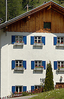 White house with blue shutters window boxes and wooden eaves. Hahntennjoch pass, Imst district, Austria.