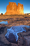 Ice patterns in the sandstone in front of the Organ, an Entrada sandstone monolith and one of the Courthouse Towers in Arches National Park, near Moab, Utah, USA, at sunrise.