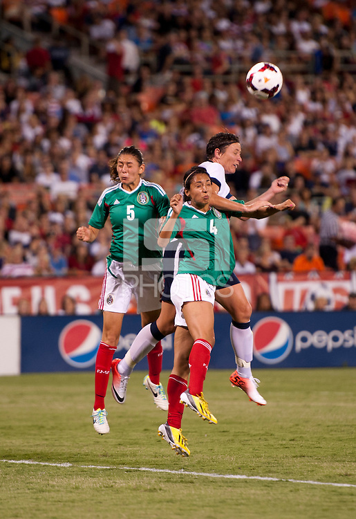 Abby Wambach (20) of the USWNT heads the ball against Christina Murillo (4) and Paulina Solis (5) of Mexico during an international friendly at RFK Stadium in Washington, DC.  The USWNT defeated Mexico, 7-0.