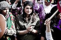 """Cette jeune femme est habillée avec l'uniforme de la guérilla. Le symbole est important car les femmes de Nusaybin sont les plus nombreuses dans la guérilla. Elles sont une inspiration pour toutes les femmes qui mènent une lutte dans la société civile.<br /> Un immense rassemblement est organisé par les femmes dans le quartier récent de Newroz à Nusaybin. Elles viennent de toute la région marquer l'espace de la ville de leur combat. L'ambiance est délirante. La foule de femme hurle et danse toute la journée. Les femmes politiques se relient sur l'estrade pour chauffer la foule. Des chansons révolutionnaires résonnent sur les toits de la ville. Le son porte évidemment jusqu'en Syrie, la frontière est à 500 mètres. Les principaux slogans sont """"nous réussirons malgré les frontières"""" et """"Jin, Jiyan, Azadî"""" qui peut se traduire par """"la femme, la vie, la liberté""""."""