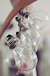 Six bulbs tied together with string hanging from a wooden hanger