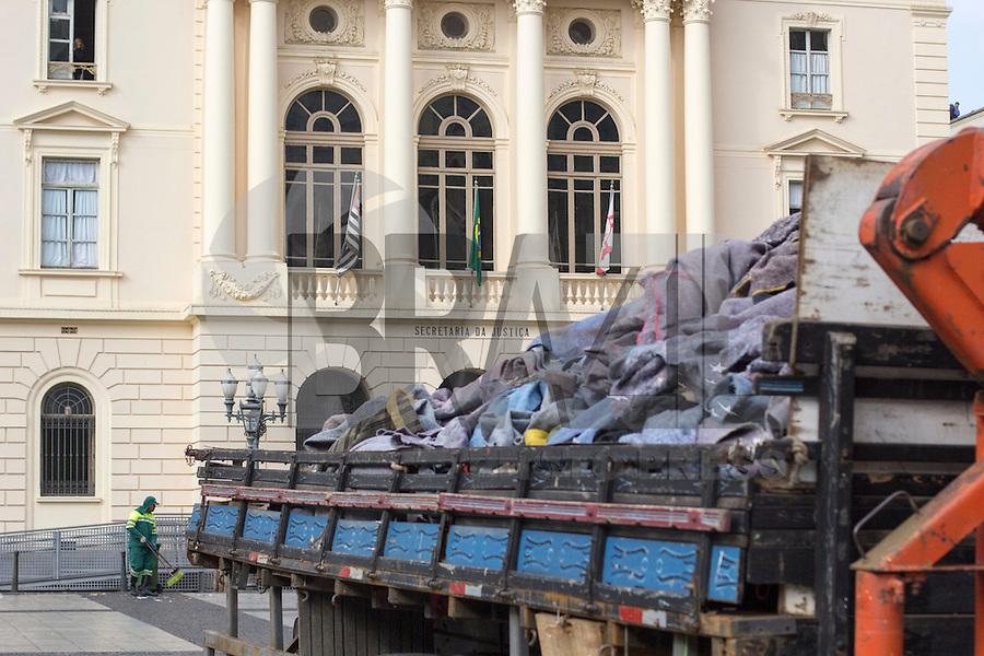 SÃO PAULO, SP, 22.06.2016 - CLIMA-SP- Funcionários da Prefeitura retiram cobertores deixados no Pateo do Collegio, na região central de São Paulo, na manhã desta quarta-feira (22). Desde a semana passada, o centro de São Paulo tem amanhecido com montanhas de cobertores usados por moradores de rua. Após a morte de seis moradores de rua durante a recente onda de frio, o prefeito assinou um decreto proibindo a GCM de retirar à força de moradores de rua pertences pessoais, carroças e itens considerados de sobrevivência, como colchões, cobertores e barracas. A regra não impede que materiais sejam recolhidos se estiverem abandonados. (Foto: Adailton Damasceno/Brazil Photo Press)