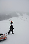 boy enjoys tubing, one of many outdoor winter activities at Copper Mountain Ski Resort, Copper Mountain, Colorado, USA