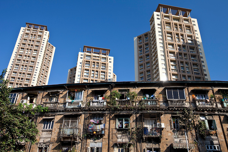 Old traditional tenement housing in shadow of new modern high rise apartment blocks at Mahalaxmi in Mumbai, India