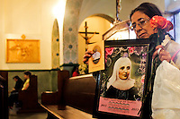 "A woman holds a picture of the saint Laura of Saint Catherine of Siena known as ""Madre Laura"" at her mausoleum in Jerico, Colombia. May 12, 2013. Photo by Freddy Builes / VIEWpress."