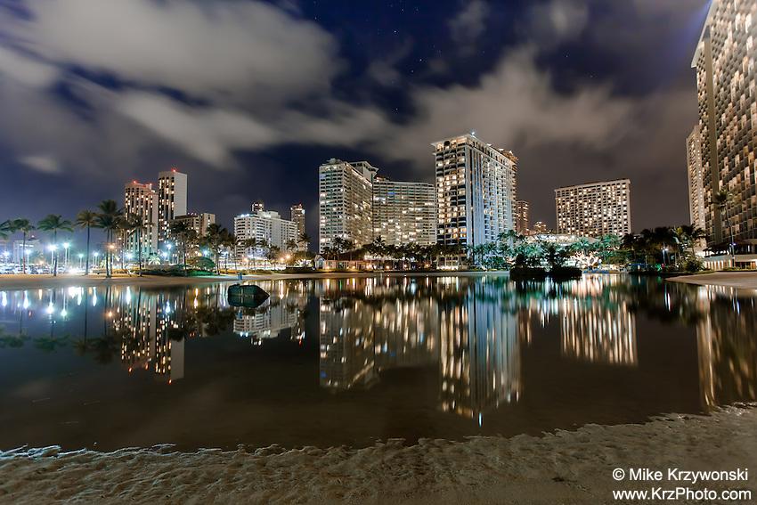 Hotels with lights reflecting off the water at night at Duke Kahanamoku Lagoon in Waikiki, Oahu