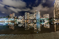 Hotels with lights reflecting off the water at night at Duke Kahanamoku Lagoon in Waikiki, Oahu