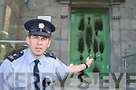Garda Eddie Walsh points to the damage caused to the front door of Killarney Courthouse after an arson attack on Monday night