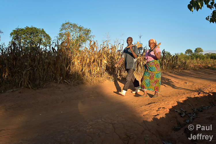 Pressing Moyo and his wife Mariet Hara walk to their farm in Edundu, Malawi. They and other farmers in the village have benefited from intercropping and crop rotation practices they learned from the Malawi Farmer-to-Farmer Agro-Ecology project of the Ekwendeni Mission Hospital AIDS Program, a program of the Livingstonia Synod of the Church of Central Africa Presbyterian.