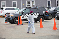 A medical worker wearing a facemask walks past a police car as COVID-19 drive-through testing takes place in a parking lot near the Cambridge Health Alliance Women's Health Hospital in Somerville, Massachusetts, on Mon., March 23, 2020. Patients could make appointments to drive through the parking lot to get tested for the virus during the ongoing Coronavirus (COVID-19) global pandemic. This location is one of a handful of such testing facilities that have opened in the Boston area in the past week.