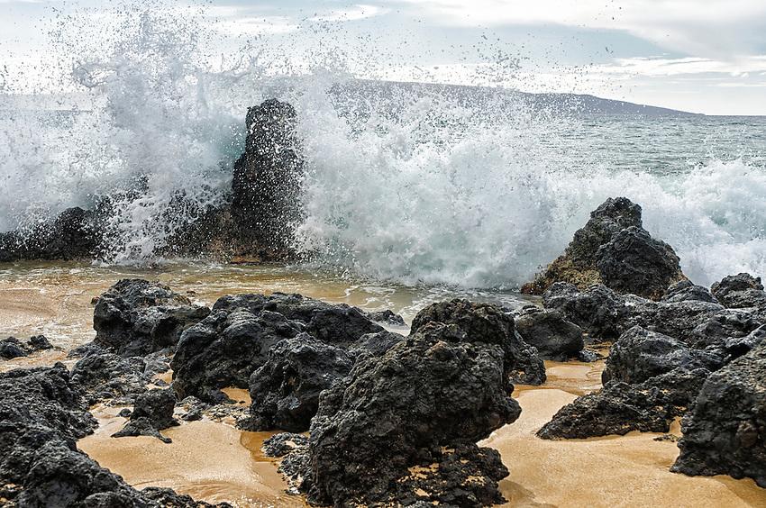 View of ocean waves crashing against lava rocks on the beach at Big Beach, Makena State Park, Maui, Hawaii